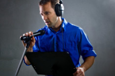 stock-photo-51574414-male-voice-over-artist-or-singer-with-a-microphone